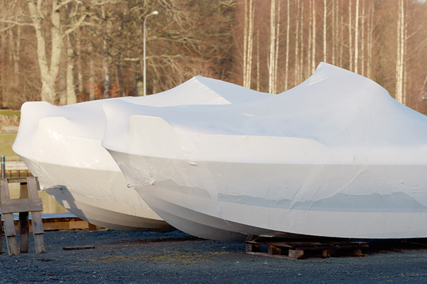 two boats with winter covers on them