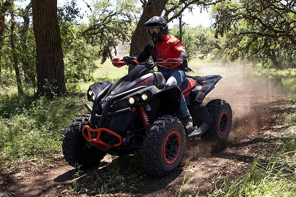 person riding the 2020 Can-Am Renegade in red color through a forest