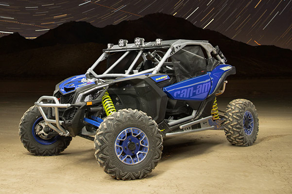 blue 2020 Can-Am Maverick X3 UTV in the dessert with mountains in the background at night