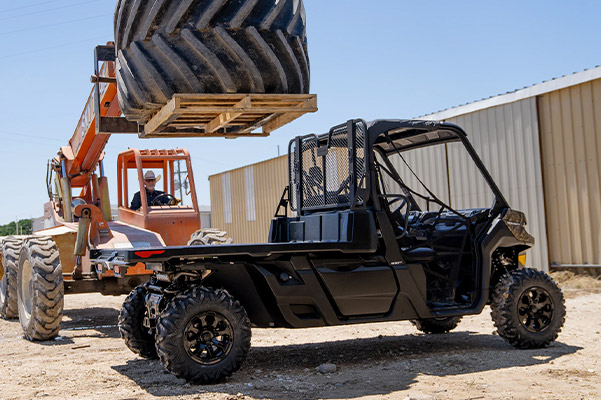 orange tracktor loading a heavy machinery tracktor tire on the back of a black 2020 Can-Am Defender UTV